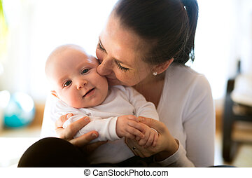 Beautiful mother holding her cute baby son - Beautiful...