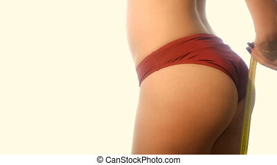 beauty woman in red sports panties measure her waist in...