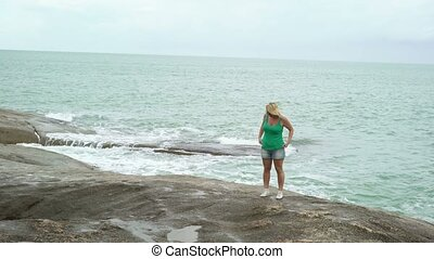 Young woman staying near sea - Young blonde woman staying...