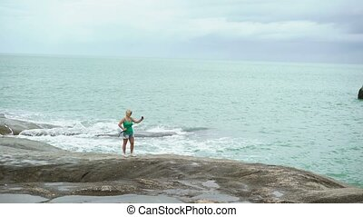 Young woman taking photo with selfie stick near sea on rocks