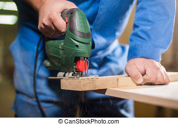 jig saw work - a carpenter worknig with jig saw and wood