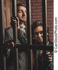 Gentleman and a lady behind bars in the prison.