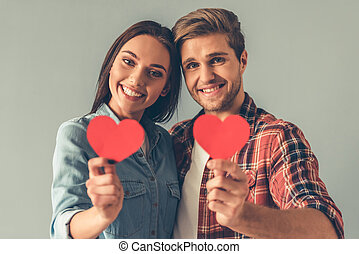 Happy young couple is holding red paper hearts, looking at...