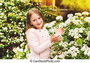 Outdoor portrait of 7-8 year old pretty little girl with...