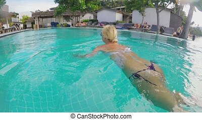Young sexy woman swimming in pool - Young blonde sexy woman...