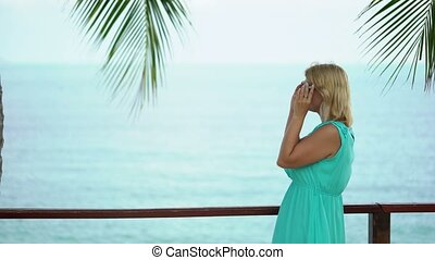 Young woman staying on embankment near sea at sunny day