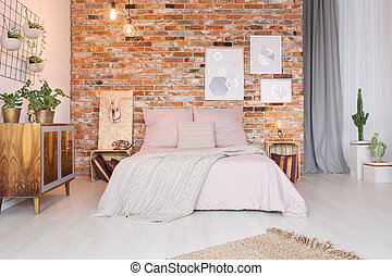 Cozy bedroom with double bed, ethnic commode and brick wall