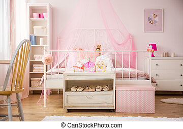 Pink bedroom with canopy bed and white furniture