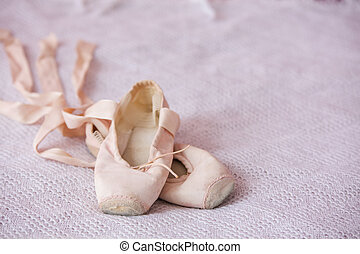 Small ballet shoes isolated on pink background