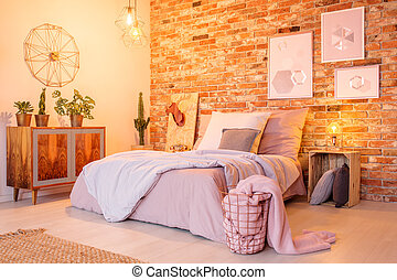 Warm bedroom with brick wall, double bed and wood commode