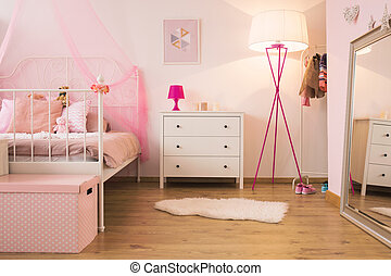Pink child bedroom with lamp, white dresser and bed