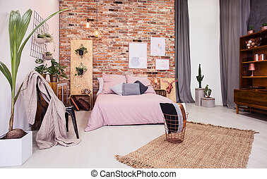 Dusty pink bedroom with bed and red brick wall