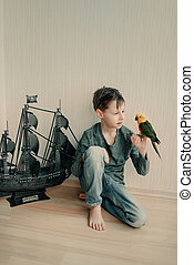 boy pirate with a parrot and a sailboat