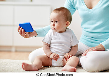 mother showing smartphone to baby at home - family,...