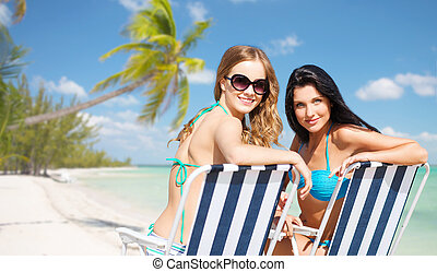happy women sunbathing in chairs on summer beach - summer...