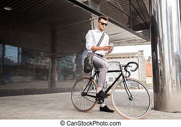 man with bicycle and smartphone on city street - lifestyle,...