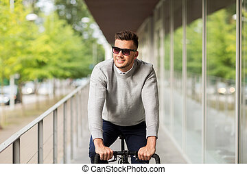 young man in shades riding bicycle on city street -...