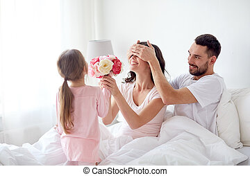 happy girl giving flowers to mother in bed at home