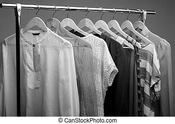 black and white photo of womens clothes on hangers. closet...