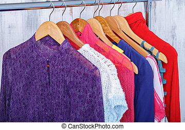 colorful womens clothes on hangers on rack in fashion store....