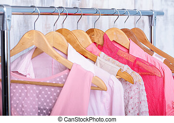 pink womens clothes on hangers on rack in fashion store....