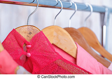 pink lace women's blouse on hangers on rack in fashion...