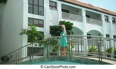 Young woman walking on a bridge in resort - Young woman...