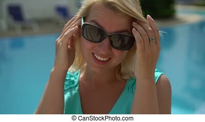 Sexy blonde woman wearing sunglasses and smile