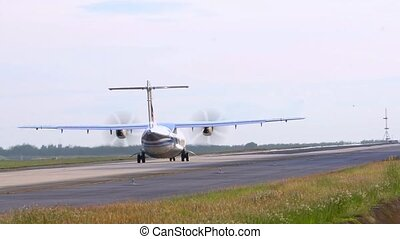 Propeller, twin-engine aircraft rolls on the runway. Day....