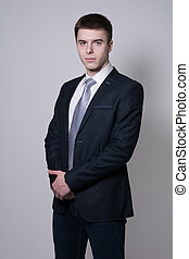 Portrait of confident business man on a gray background....