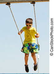 Boy playing swinging by swing-set. - Rest and relax for...