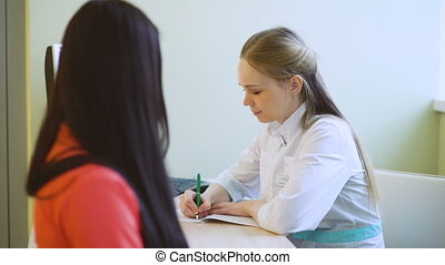 Female doctor explaining something to female patient and write diagnosis