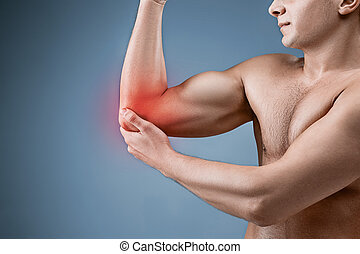Man With Pain In Elbow. Pain relief concept on gray studio...