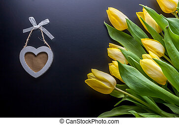 yellow tulips and wooden heart - bouquet of yellow tulips...