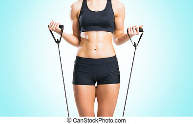 Fit, healthy and sporty woman in sportswear doing expander...