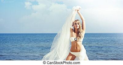 Sexy, beautiful, young girl in alluring bikini with a...