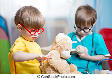 Kids playing doctor and curing plush toy indoors