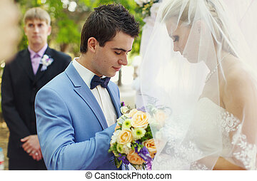 Groom puts on a ring on the wedding ceremony