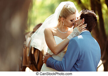 Romantic kiss in the park in the wedding day