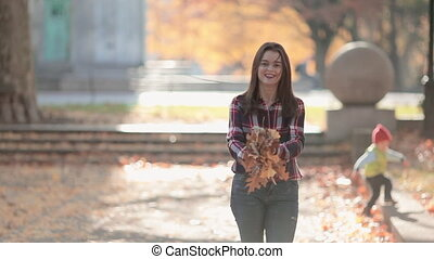 Autumn woman throwing fall leaves having fun laughing, playing colorful forest foliage outdoors. Joyful girl in red