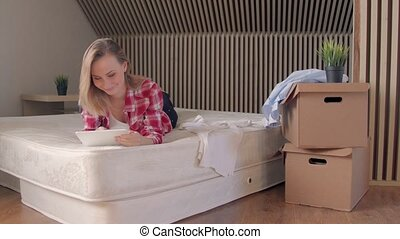 Woman lying on the mattress in her new flat and using on...