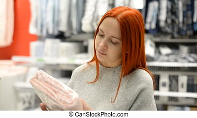 Attractive red girl shopping for bedding