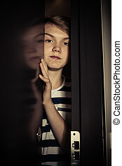 Teenager boy behind ajar door - Close-up view of emotionless...