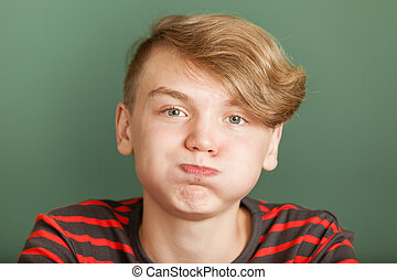 Boy puffing cheeks - Close-up portrait of handsome teenager...