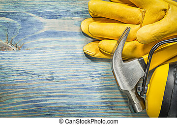 Composition of protective workwear claw hammer on wood board...