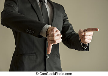 Businessman giving a thumbs down negative vote to show his...