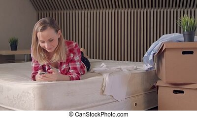 Smiling young woman using her phone in new house