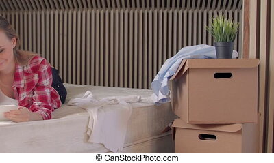 Woman takes a break from unpacking new apartment with...