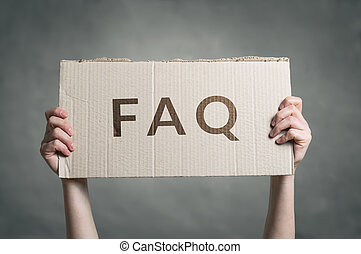 FAQ - Frequently Asked Questions text on cardboard held