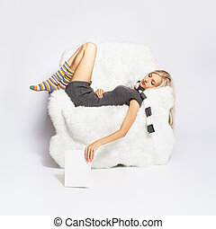 girl sleeping in arm-chair - portrait of beautiful blonde...